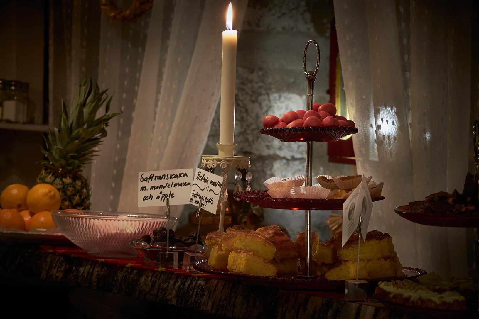 Hembakat fika uppdukat på ett bord med ett tänt stearinljus.