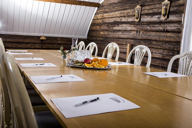 Dukat för konferens med bord, stolar, vatten och frukt.